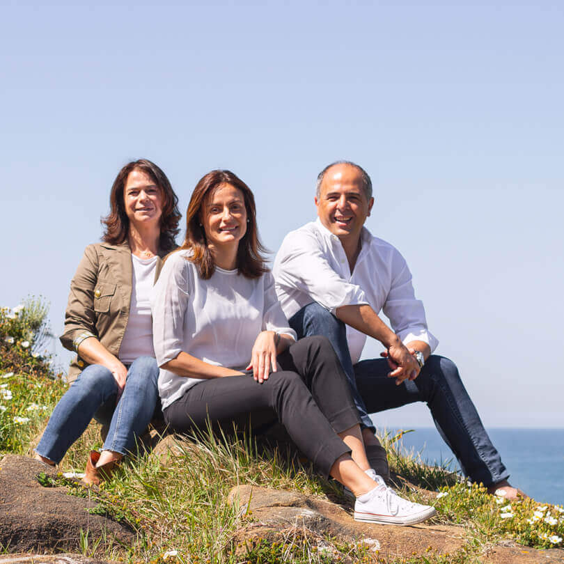 Marialma's team sitting on the edge of a rock near the seaside