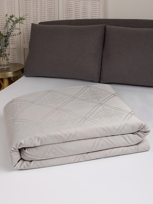 Marialma's Ice Grey Sensitive Zinc Duvet Cover with Jacquard Faro folded on top of a bed