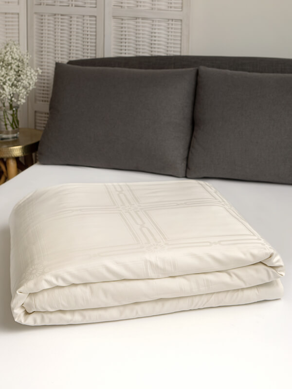 Marialma's Solid Ivory Cosmetic Algae Duvet Cover with Jacquard Liberdade folded on top of a bed