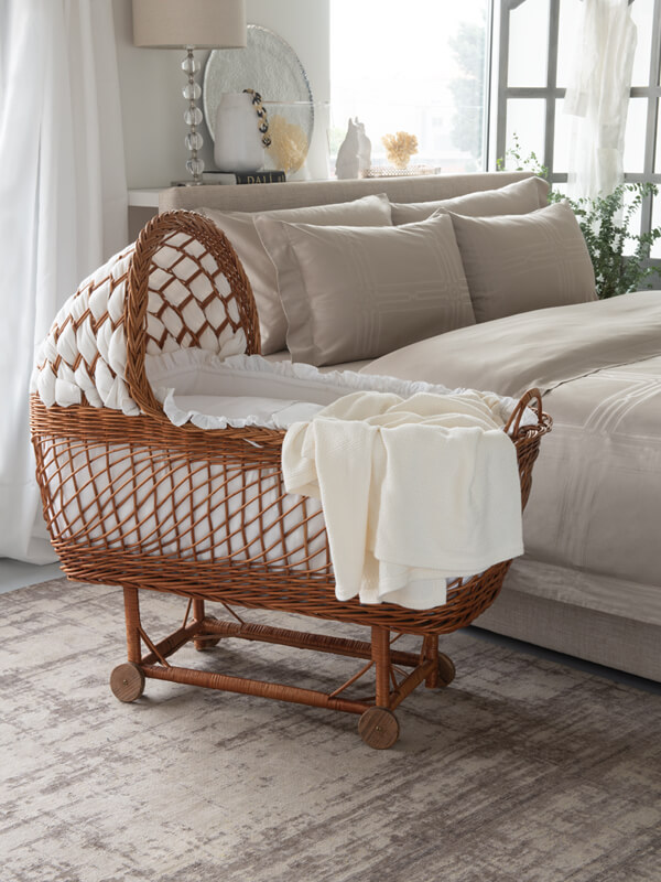 A bedroom with a crib that is made with Sensitive Zinc Bassinet Sheet Set