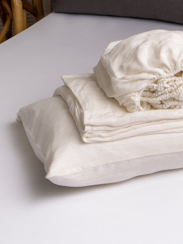 Marialma's Natural Hemp Cot Bed Sheet Set folded on top of the bed