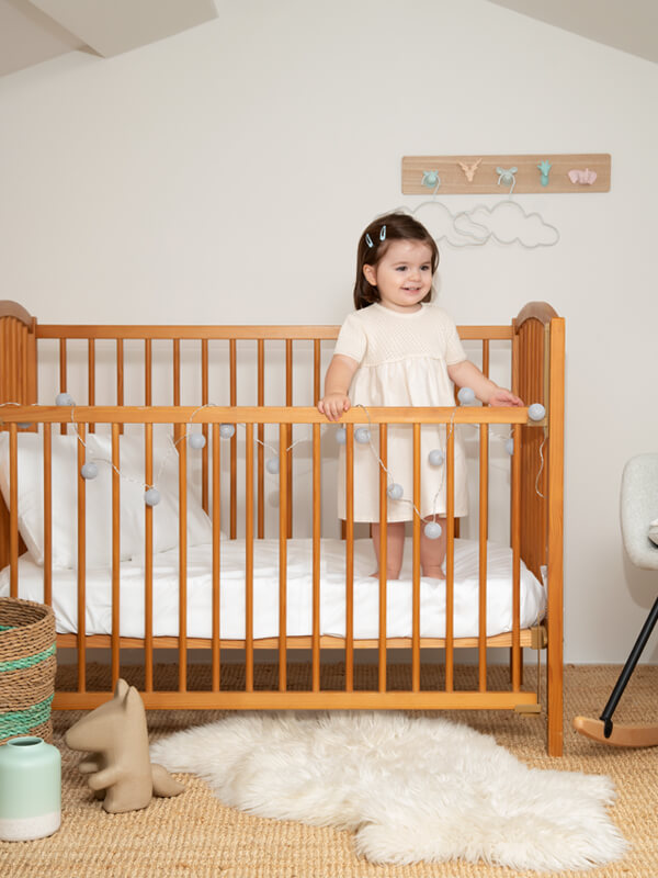 Children's bedroom with a baby girl in a crib with white Sensitive Zinc Cot Bed Sheet Set