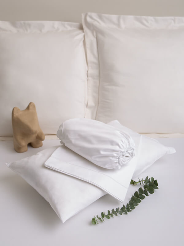 Marialma's White Sensitive Zinc Cot Bed Sheet Set folded on top of a bed with a green plant and a wooden toy