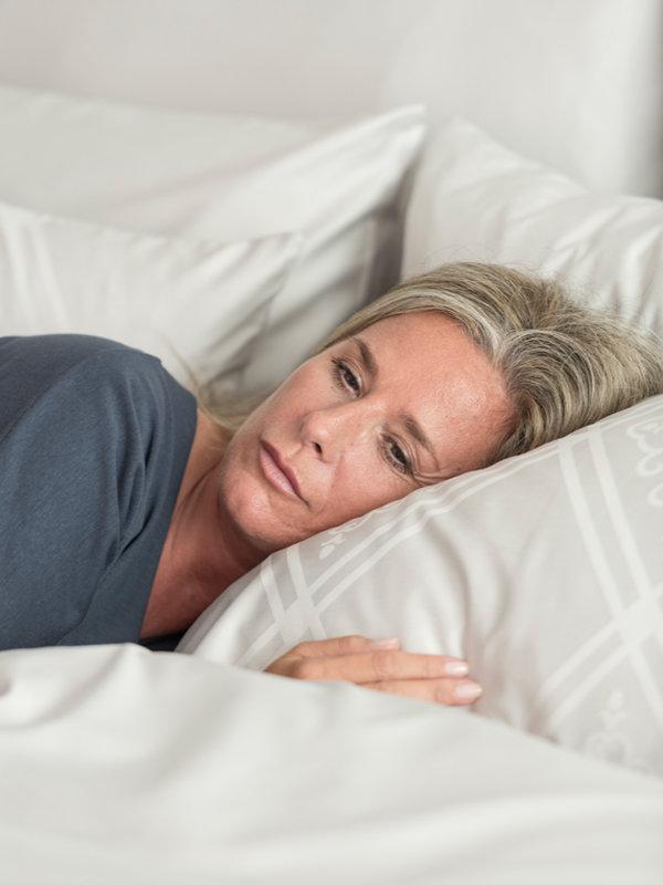Sleepy middle-aged woman lying in Marialma's Grey Faro Sensitive Zinc Pillowcase with Jacquard Faro