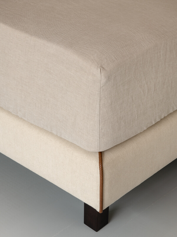 Detail of the corner of a bed with Marialma's Natural Hemp Fitted Sheets