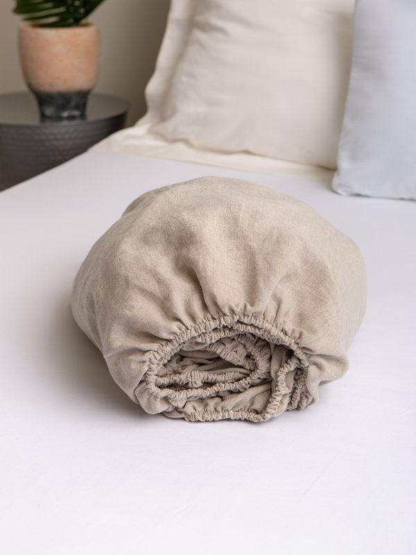 Marialma's Natural Hemp Fitted Sheet folded on top of a bed
