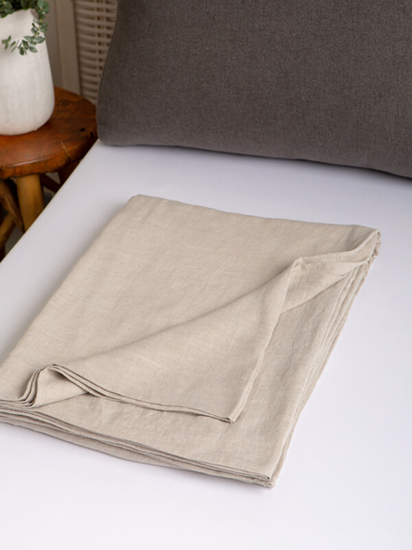 Marialma's Natural Hemp Flat Sheet folded on top of a bed