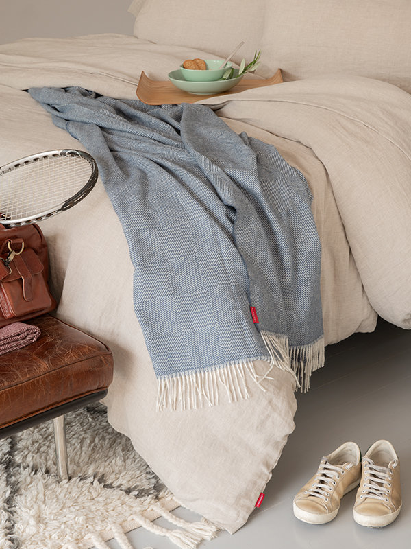 Bed with Marialma's blue alpaca throw and Natural Hemp Bedding Set with a wooden tray with breakfast on top