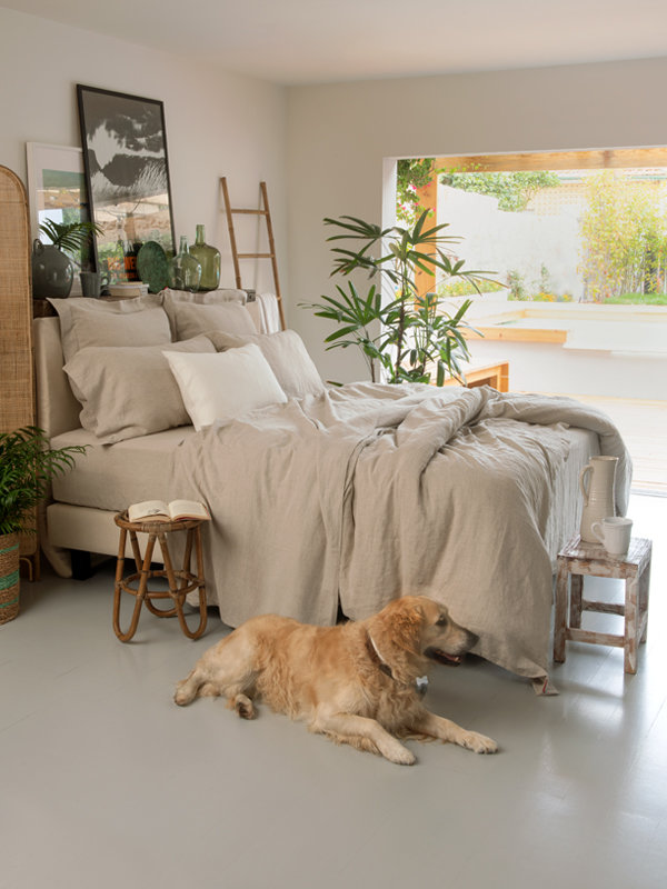 Bedroom featuring bed with Marialma's Natural Hemp Bed Sheet Set and dog near the bed