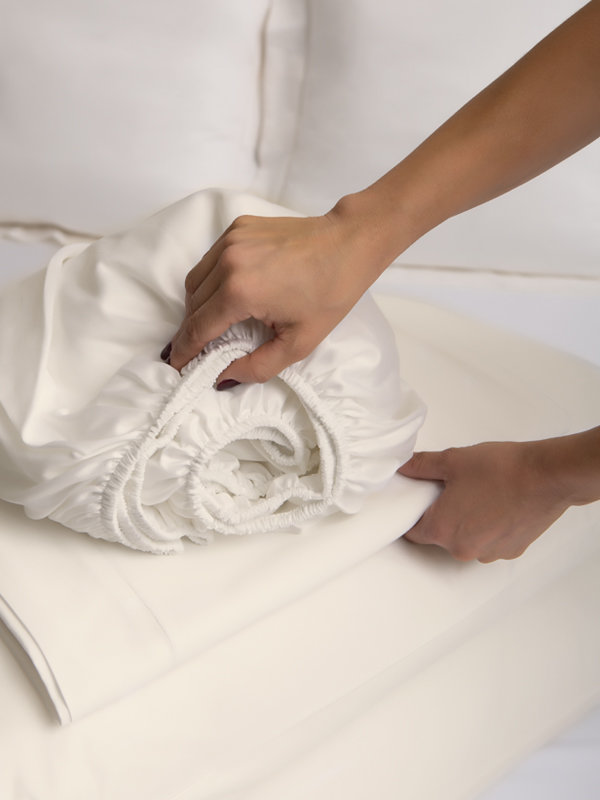 Woman picking up Marialma's Ivory Cosmetic Algae Sheet Set folded on top of a bed