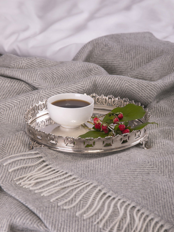 A silver tray with a cup of coffee on top of Marialma's grey alpaca throw
