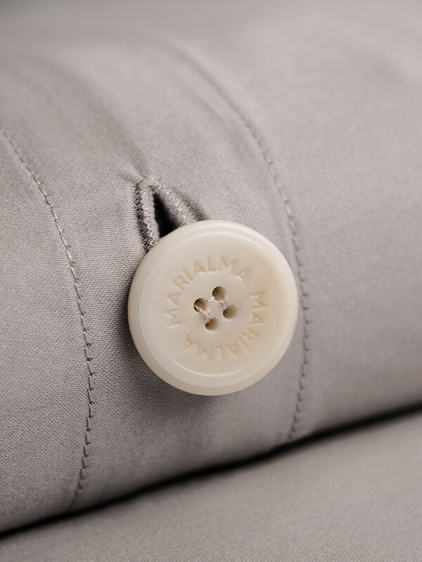 Detail of a Marialma's biodegradable button from a Grey Sensitive Zinc Duvet Cover