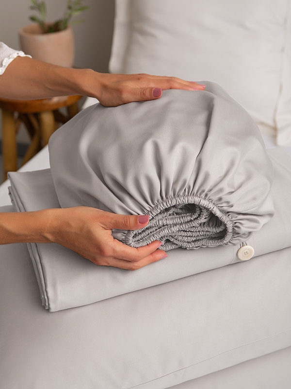 Woman with her hand on Marialma's Grey Sensitive Zinc Fitted Sheet on top of a bed