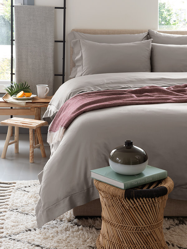A bedroom design that features Marialma's Grey performance bedding and alpaca throw