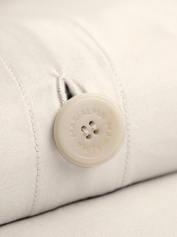 Detail of a Marialma's biodegradable button from an Ivory Cosmetic Algae Duvet Cover