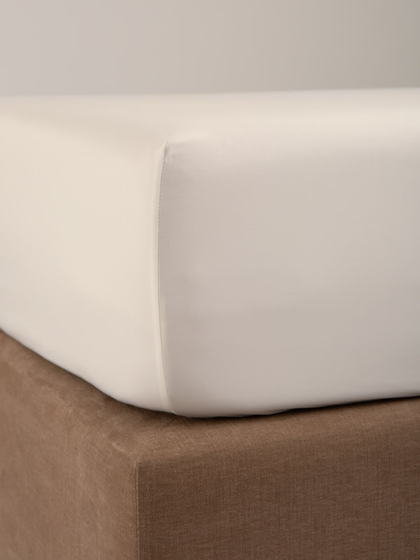 Detail of the corner of a bed with Marialma's Ivory Cosmetic Algae Fitted Sheet
