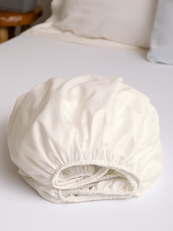 Marialma's Ivory Cosmetic Algae Fitted Sheet folded on top of a bed