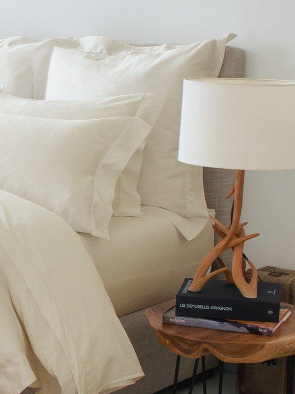 Bedroom featuring wooden table lamp and side table with bed with Marialma's Ivory Cosmetic Algae Fitted Sheet