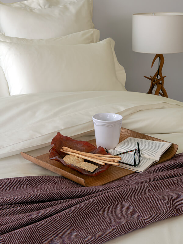 Marialma's Ivory Cosmetic Algae Sheet Set with Bordeaux Throw and wooden tray with breakfast and book on top