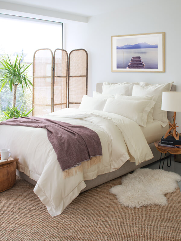A bedroom design that features Marialma's Ivory Cosmetic Algae Fitted Sheet and alpaca throw