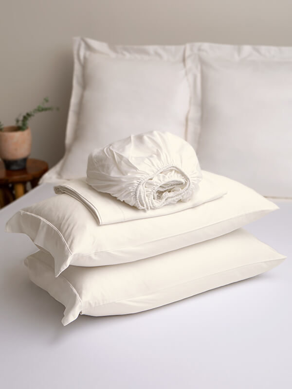 Marialma's Ivory Cosmetic Algae Sheet Set folded on top of a bed