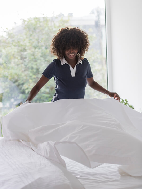 Woman making a bed with Marialma's White Performance Bedding