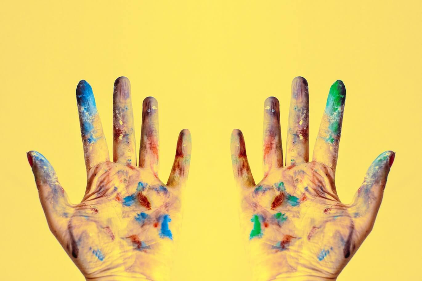 two hands filled with painting on a yellow background