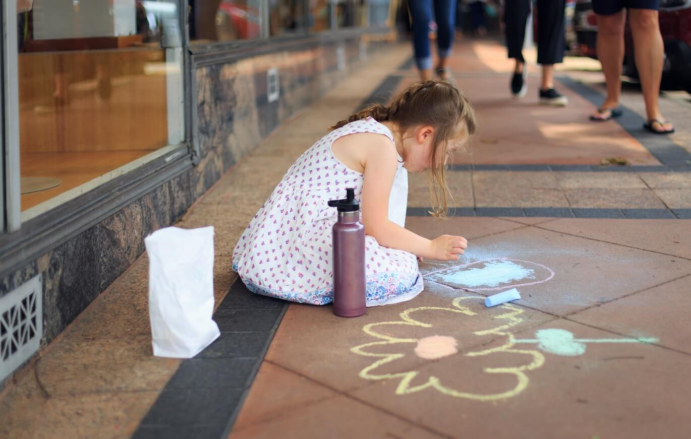 young girl drawing on the floor using chalks