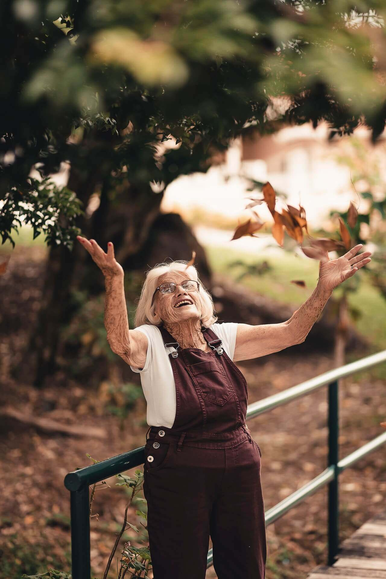 Happy old lady with brown overalls throwing brown leaves in the air in a park.
