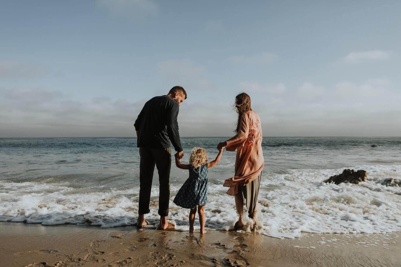 happy family holding hands near the sea