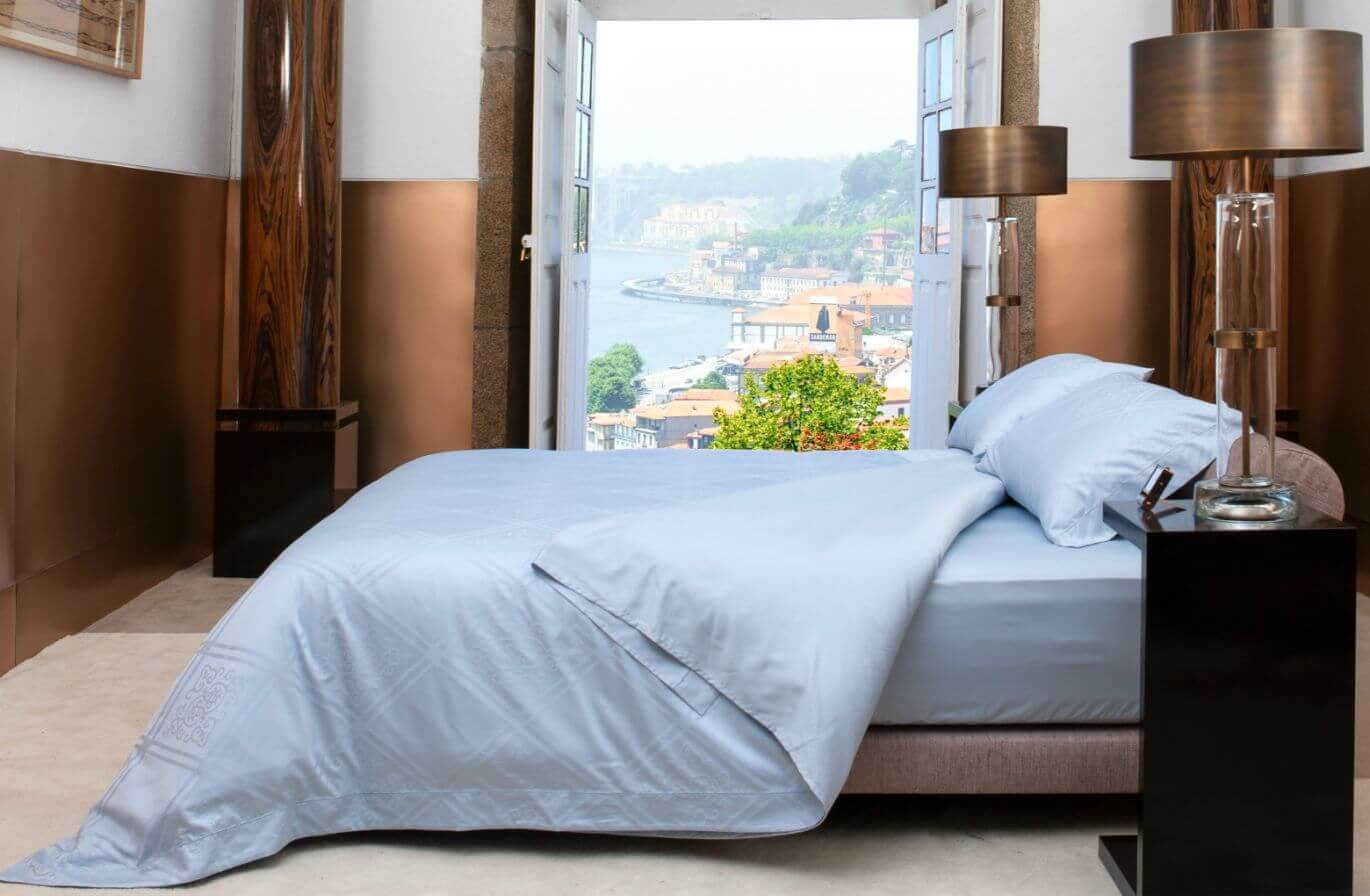 bedroom with a view over the city of Porto and a bed with white bed sheets