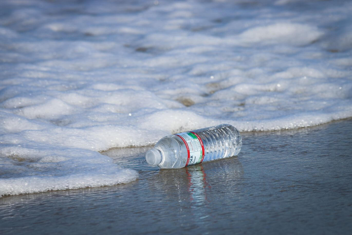 microplastic pollution through a plastic bottle washed ashore on a beach
