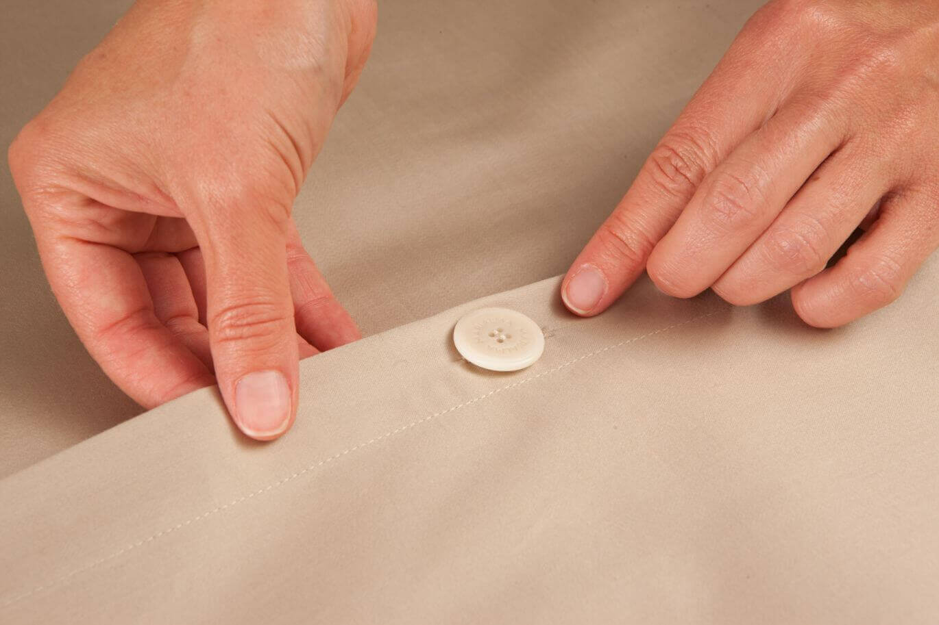 close up of button from beige bed sheets by marialma