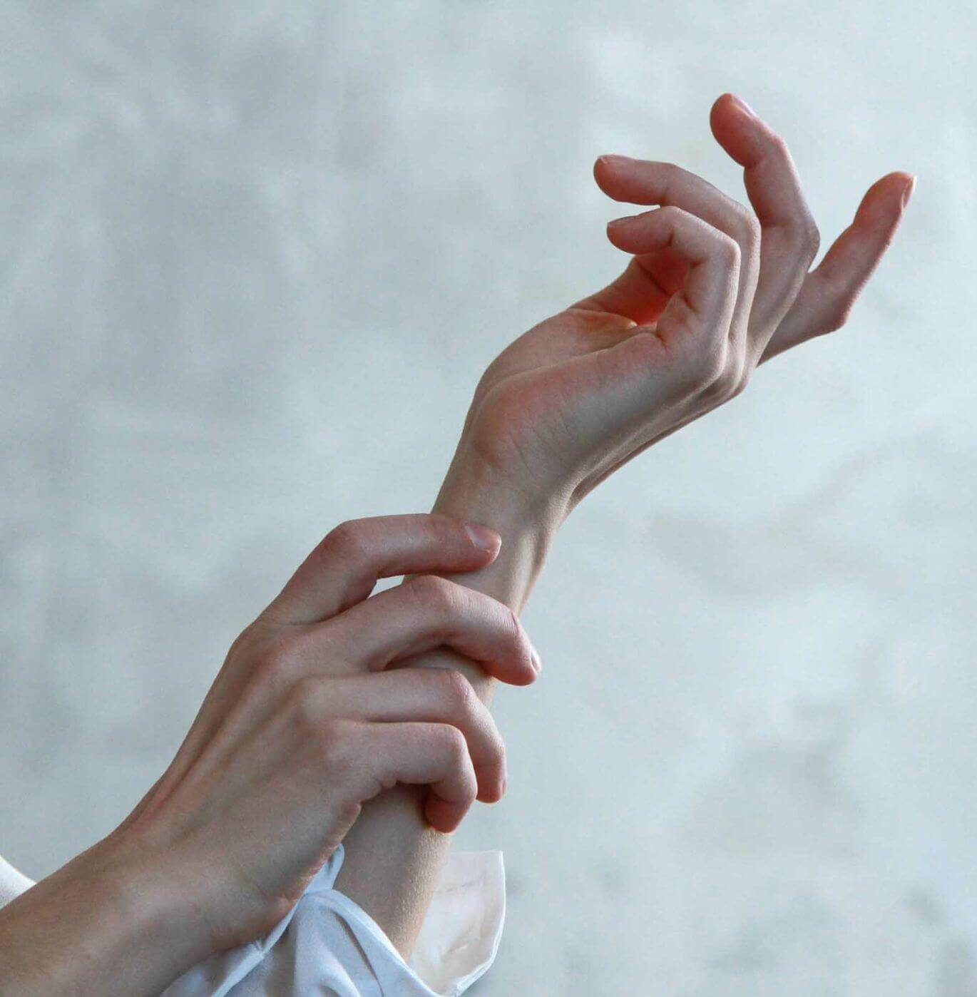 Blurred background with a close-up of two hands with dry skin