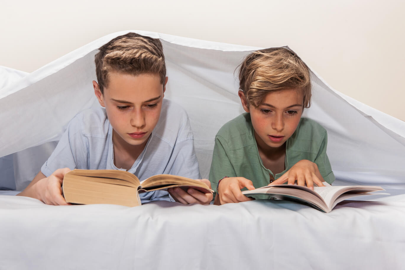 two boys reading books under a white bed sheet
