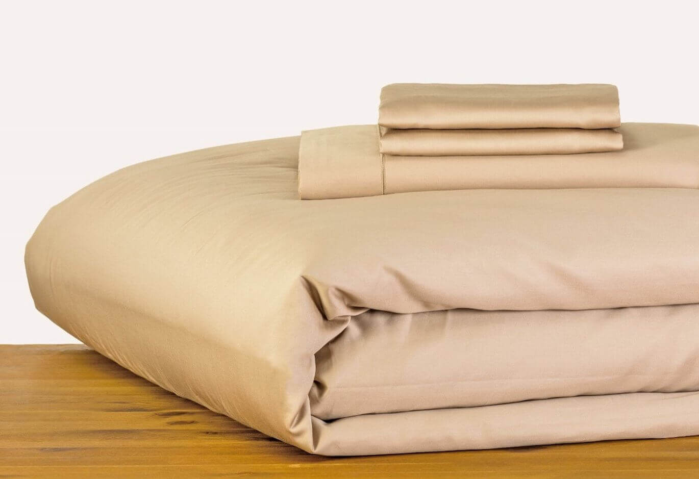marialma's beige bed sheets on a wooden table