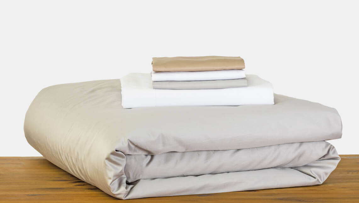 A mixture of white and beige bed sheets from Marialma on a wooden table.