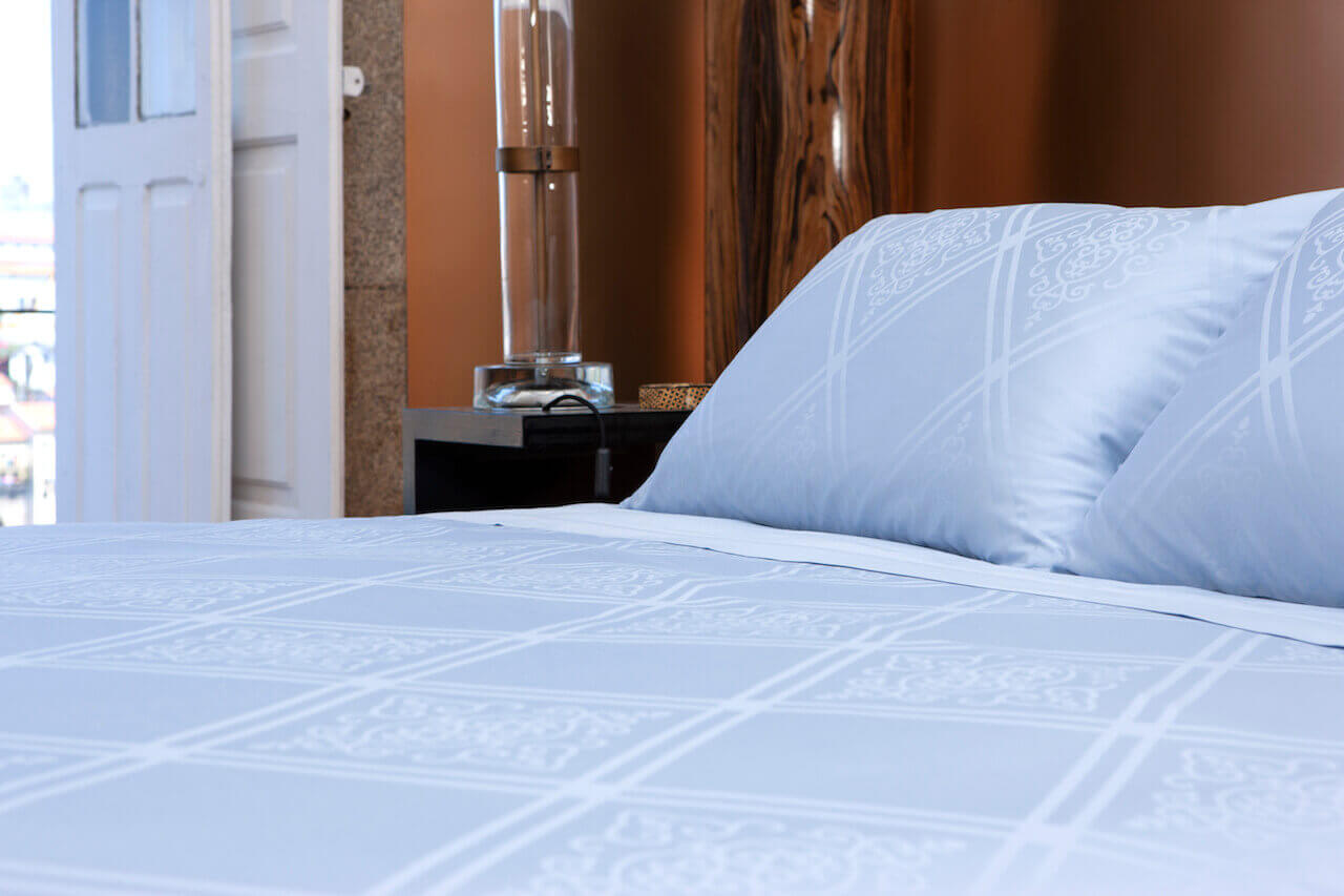 A bedroom that features a zinc oxide bedding set with a Portuguese Sidewalk white pattern.