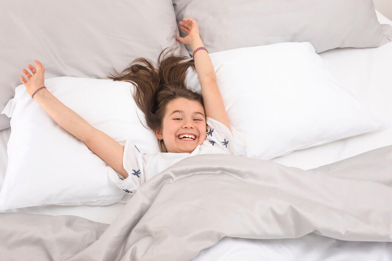 Happy kid stretching in her bed with white and gray pillows and bed sheets