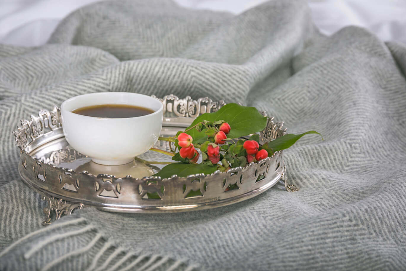 a cup of tea on a tray on top of a grey throw