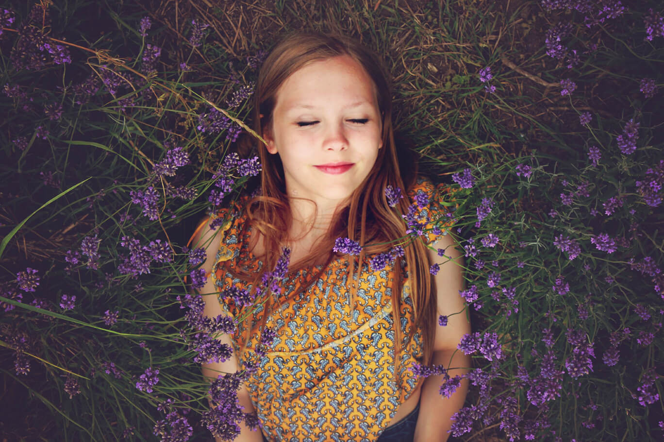 A girl that is sleeping in the back sleeping position in a field filled with purple flowers