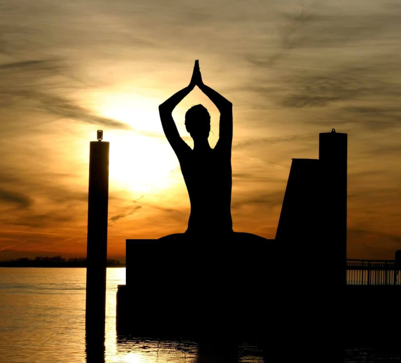 Silhouette of a woman doing a meditation pose during sunset