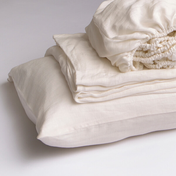 Marialma's natural hemp cot bed sheet set folded on top of a bed