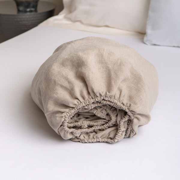 Marialma's natural hemp fitted sheets folded on top of a bed