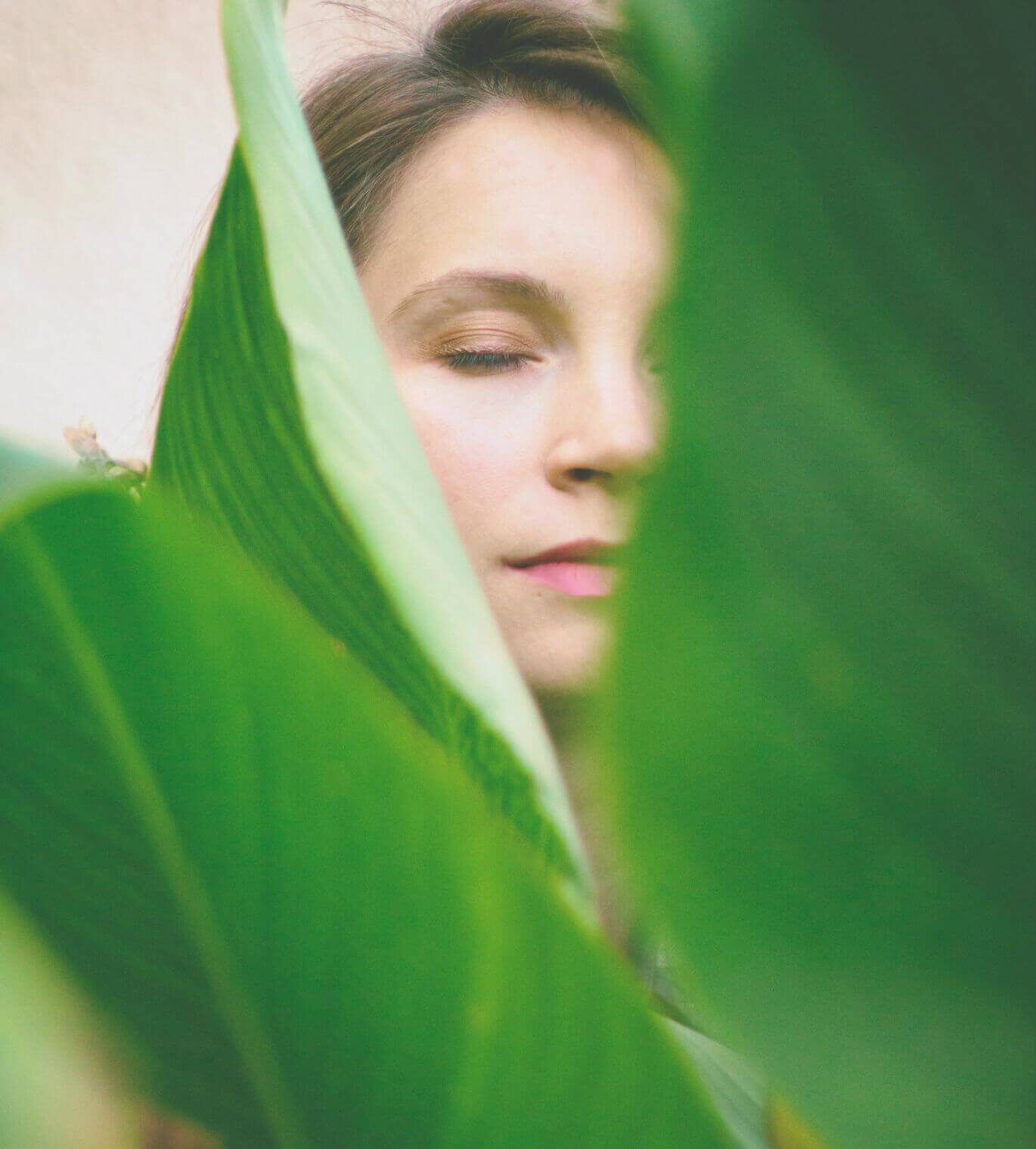Big green leaves with a peaceful woman with closed eyes in the background.