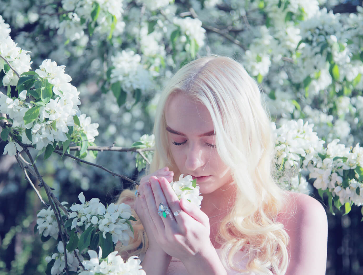 blonde woman smelling white flowers