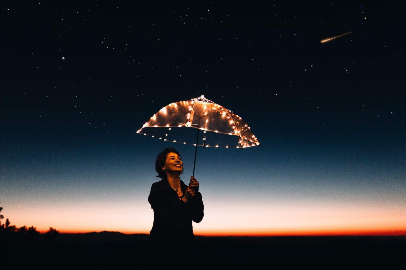 Woman with an umbrella looking to the sky filled with shooting stars