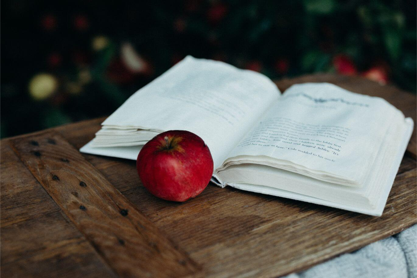An open book with bedtime stories with a red apple next to it