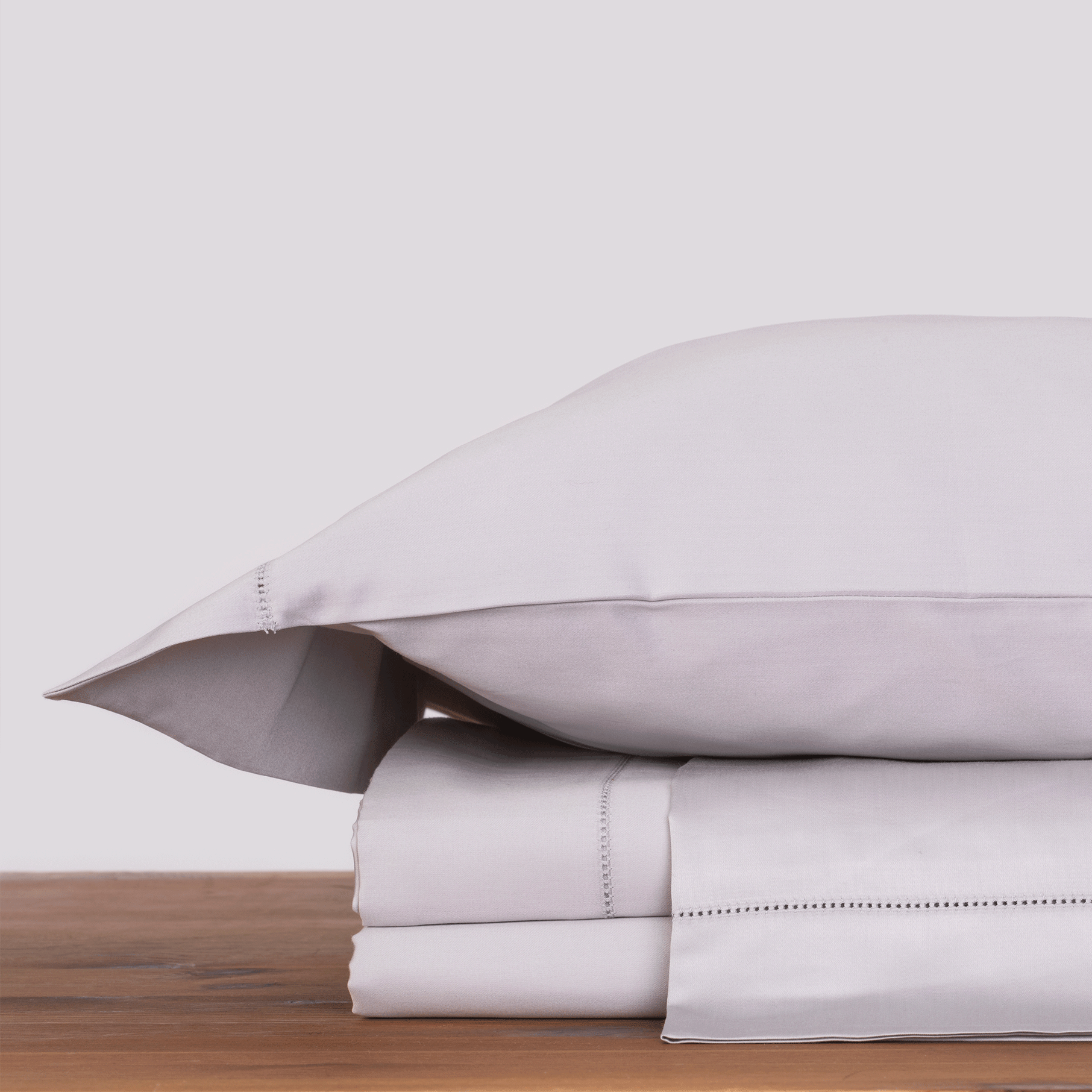 white pillow and folded performance bed sheets from Marialma