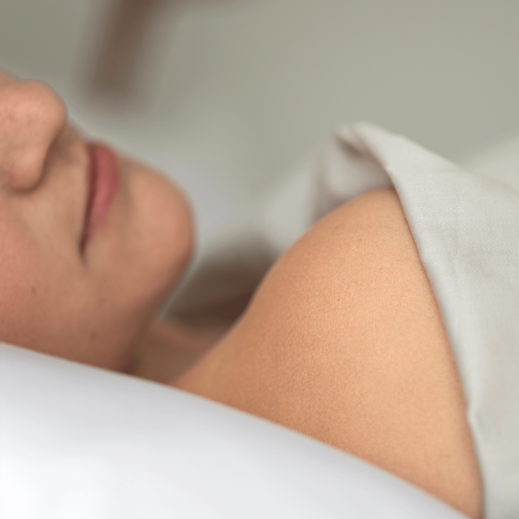 Woman's shoulder in touch with performance bed sheets